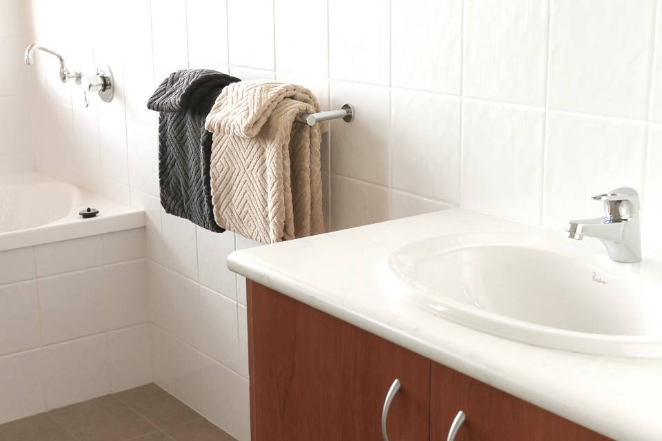The white tiled bathroom of the Redgum chalet with basin, towel rail, towels and bath.