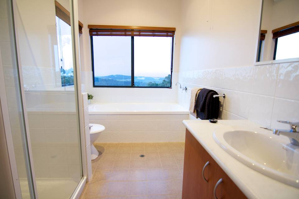 The bright white bathroom of the Karri chalet with shower, bath, basin and toilet.