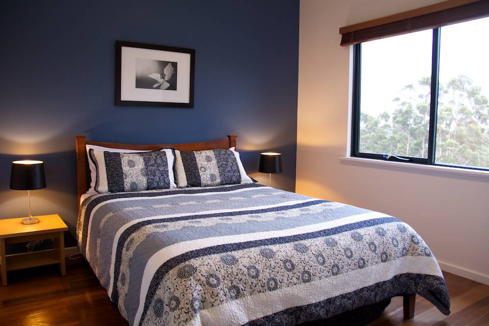 The bedroom in the Karri chalet with side lamps, a double bed and large window looking out to huge trees.