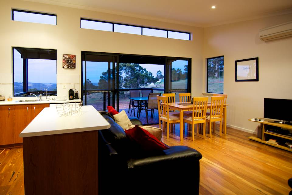 The lounge and dining area of the Karri chalet with wooden table and chairs and black leather couches.