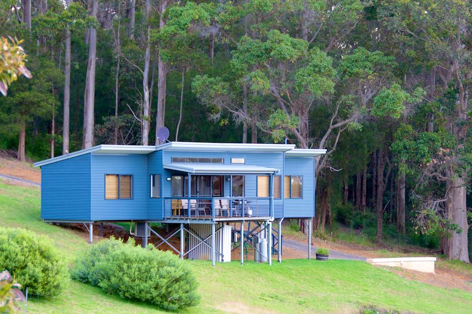 The outside of the Karri chalet with lush green grass and the karri forest behind.