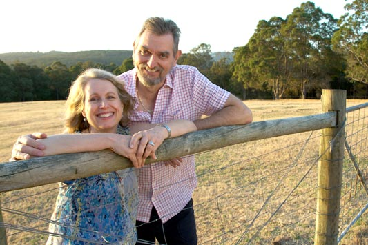 John and Rhonda standing together leaning on a fence
