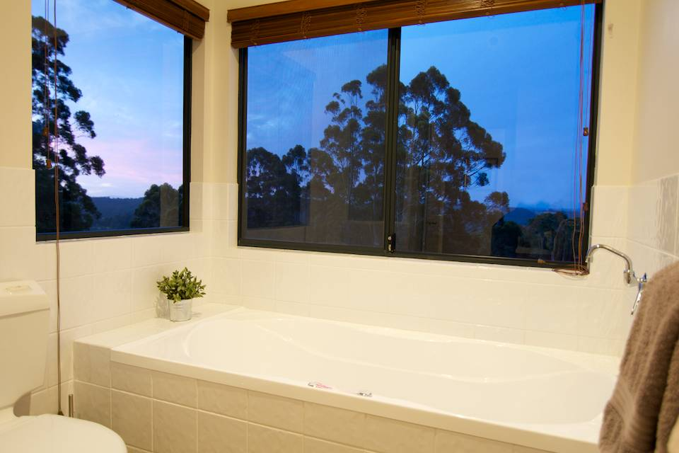 The bath in the Tingle chalet with windows looking out to the sunset.