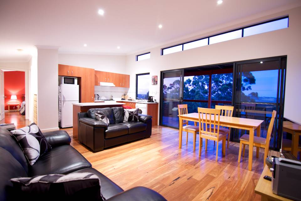 A black leather couch, beautiful wooden floors and a stylish kitchen.